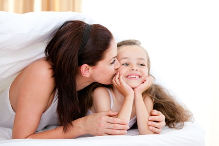 Attentive mother kissing her daughter  photo