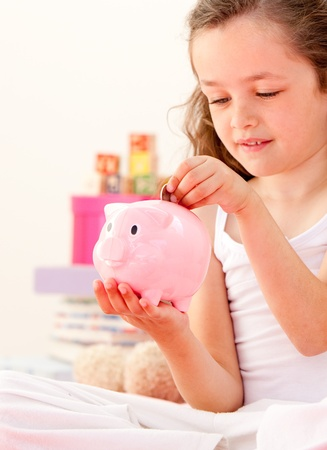 Cute little girl saving money in a piggy-bank sitting on her bed  photo