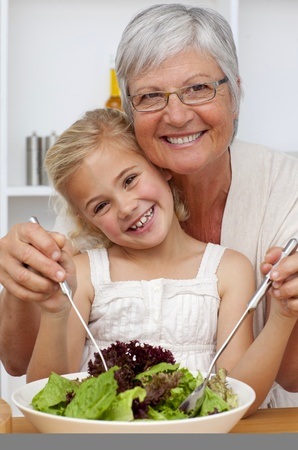 Happy grandmother eating a salad with granddaughter photo