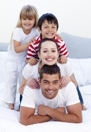 Happy family playing in bed together photo