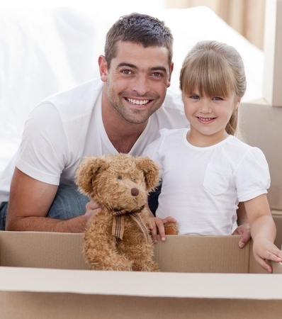 Father and daughter with a teddy bear moving home photo