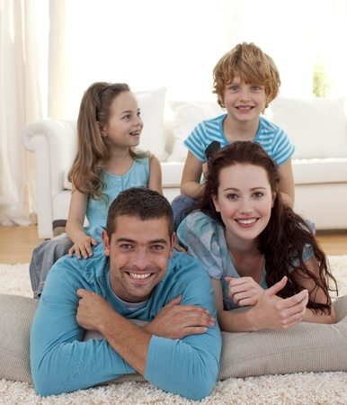 Parents, daughter and son on floor in living-room photo