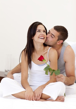 Lovers sitting on bed with a rose photo