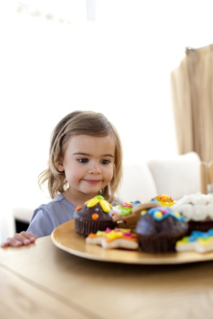 Little girl looking at confectionery at home Stock Photo - 10137524