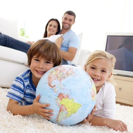 Children playing with a terrestrial globe at home photo