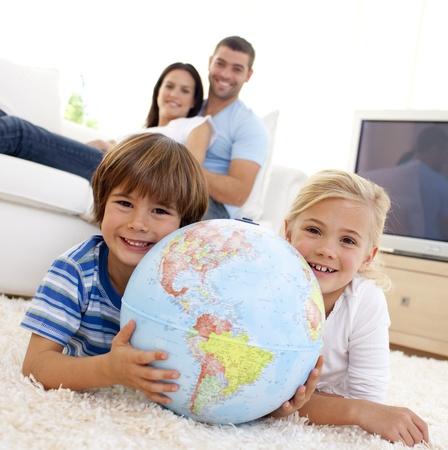 planeta tierra feliz: Niños jugando con un globo terraqueo en casa Foto de archivo