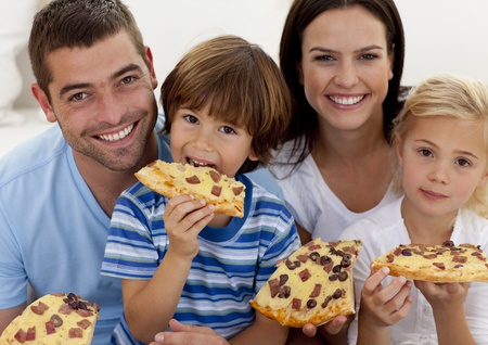 Portrait of family eating pizza in living-room photo