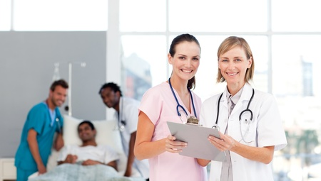 medical attendance: Attractive doctors attending to a patient Stock Photo