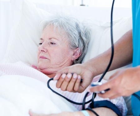 Sick senior woman lying on a hospital bed photo