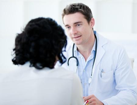 physical test: Handsome medico parla con il suo paziente per l'annuale check-up