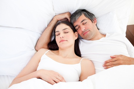 gratified: Affectionate couple hugging lying in their bed Stock Photo