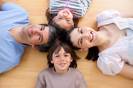 lying on the floor: Smiling young family lying on the floor with heads together