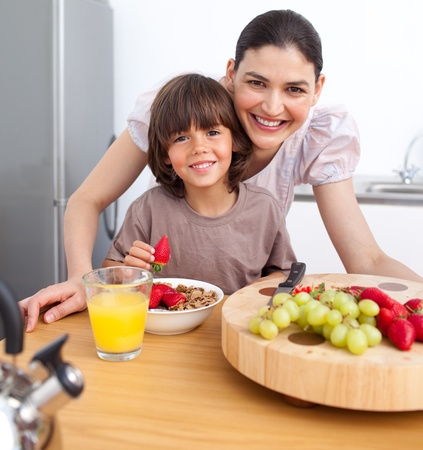 Cheerful mother and her child having breakfast photo