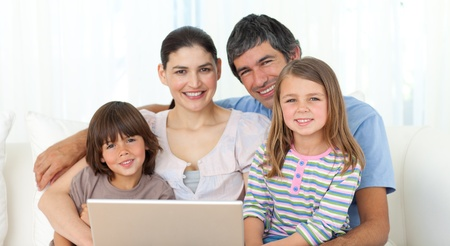 Happy family using a laptop on the sofa photo