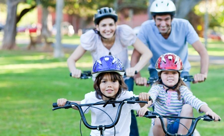 riding helmet: Familia alegre, andar en bicicleta Foto de archivo
