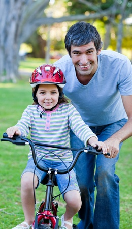 cycle ride: Cute little girl learning to ride a bike with her father Stock Photo