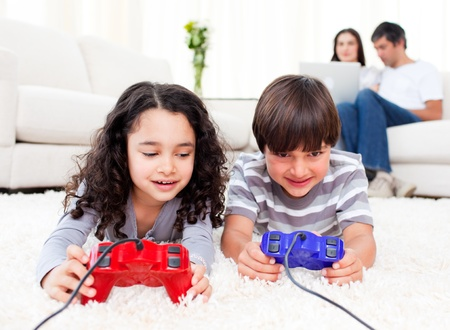 Cute siblings playing video games laying down on the floor photo