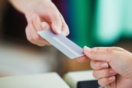 room card: Close-up of a young woman paying with her credit card