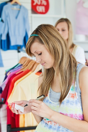 choosing clothes: Happy women choosing clothes together Stock Photo