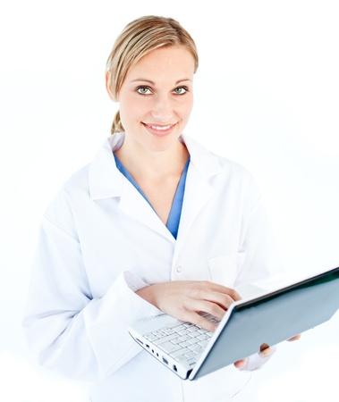Encantadora doctora sosteniendo un portátil mirando la cámara