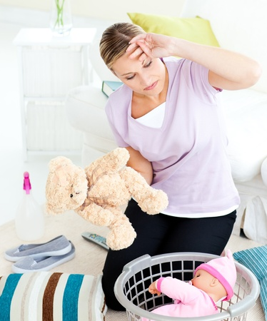 Exhausted young woman putting toys into a basket photo