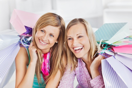 delighted: Delighted two women holding shopping bags smiling at the camera