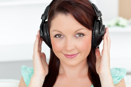 Bright woman listening to music with headphones at home photo
