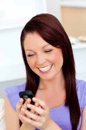 captivating: Bright woman texting with her cellphone on a sofa Stock Photo