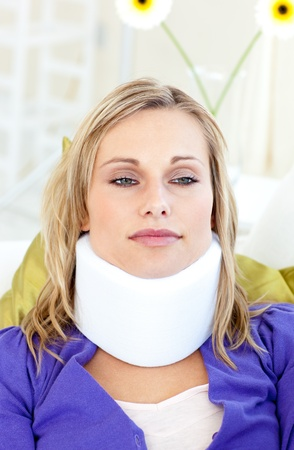 Attractive woman wearing neckbrace lying on a sofa photo