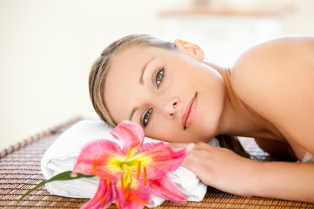 delighted: Close-up of a delighted woman lying on a massage table with a flower