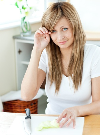 animated adult: Pretty young woman cutting onions and crying in the kitchen Stock Photo
