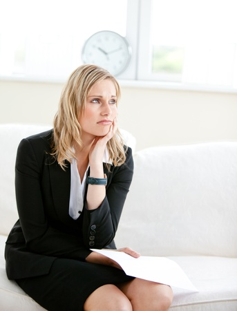 disconsolate: Annoyed businesswoman holding a paper and sitting on a sofa