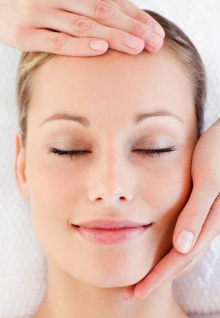 Portrait of a charming young woman receiving a head massage photo