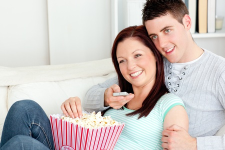 Affectionate couple lying on the sofa watching television in the living-room Stock Photo - 10175840
