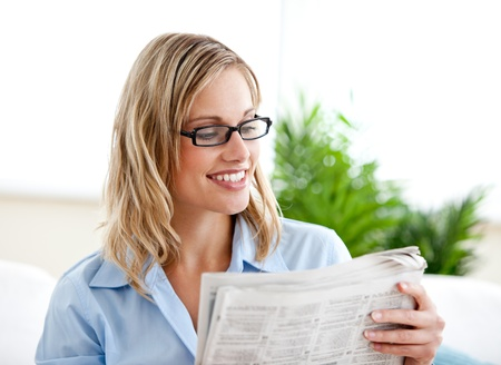 Attractive businesswoman wearing glasses and reading the newspaper sitting on the sofa photo