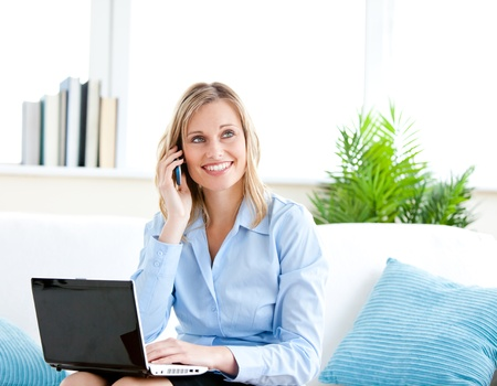 home phone: Smiling businesswoman talking on phone and using her laptop sitting on a sofa