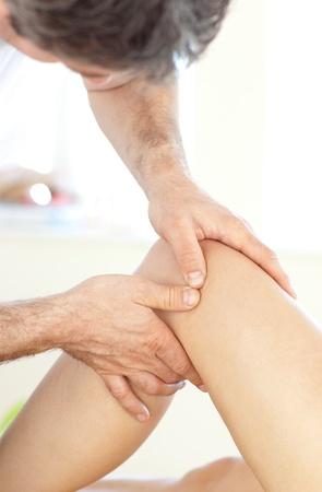 fisico: Primer plano de una joven fisioterapeuta dando un masaje de piernas
