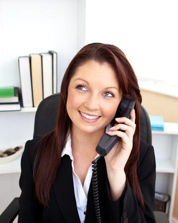 Attractive businesswoman talking on phone sitting photo