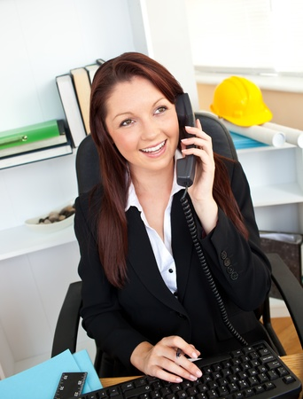 Ambitious businesswoman talking on phone using her computer photo
