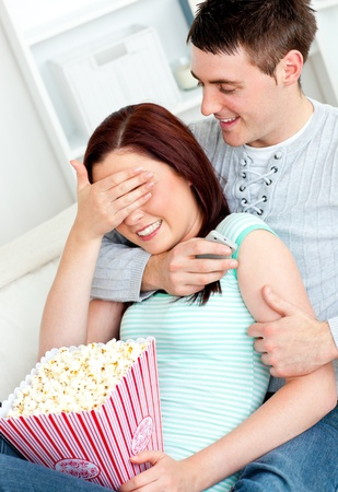 Charming couple lying on the sofa with popcorn and remote Stock Photo - 10175793