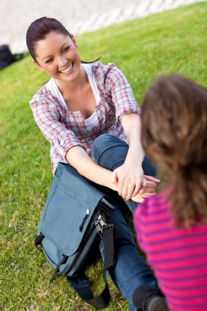 Two female students talking together sitting on the grass photo
