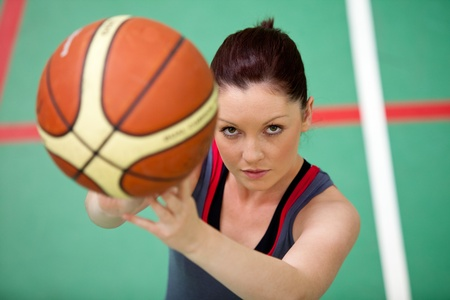 Portrait of an athletic young woman playing basket-ball photo