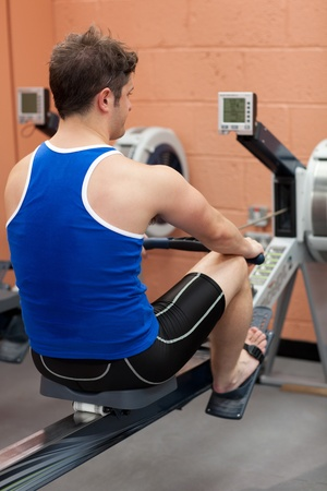 musculation: Athletic caucasian man using a rower