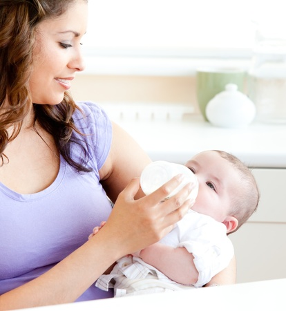 Radiant mother feeding her adorable son in the kitchen Stock Photo - 10137205