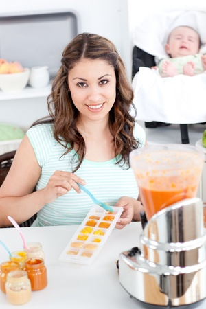 Caring mother preparing food for her lovely baby in the kitchen Stock Photo - 10171280