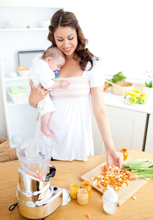 Caring young mother preparing vegetables for her baby in the kitchen photo