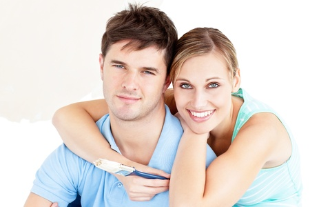 paintrush: Portrait of a young enamored couple painting their new room