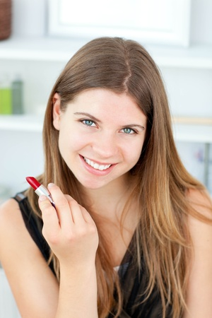 Pretty woman holding lipstick at the camera Stock Photo - 10136938