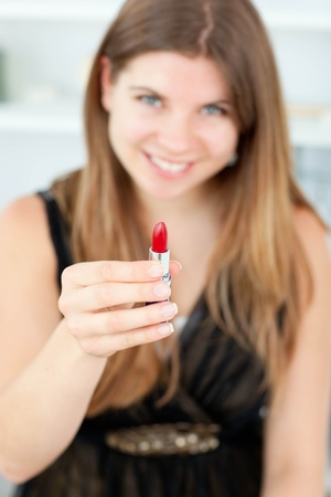 Smiling woman holding lipstick in the camera Stock Photo - 10135158