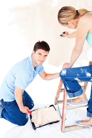 Beautiful caucasian couple painting a room